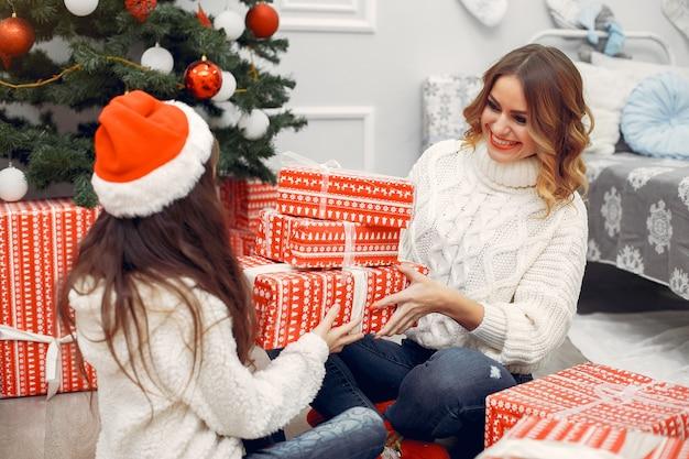 Madre con figlia carina in decorazioni natalizie