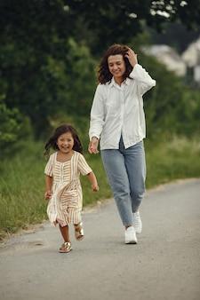 Madre con figlia che gioca in un campo estivo