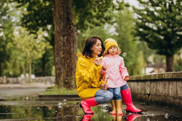 Madre con figlia divertirsi nel parco in un tempo piovoso