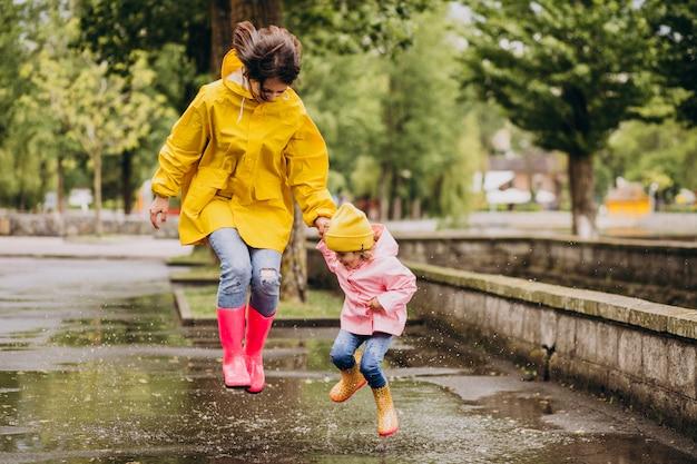 Madre con figlia divertirsi saltando nelle pozzanghere