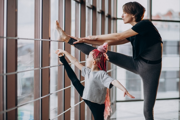 Madre con figlia piccola a praticare yoga vicino alla finestra