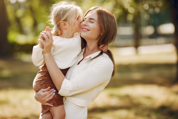 Madre con figlia piccola, giocando in un parco estivo