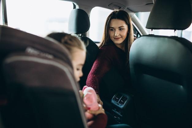 Madre con figlia piccola seduta nella parte posteriore della macchina in un seggiolino per auto
