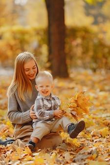 Madre con figlio piccolo, giocando in un campo in autunno