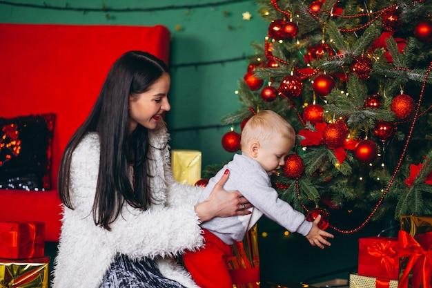 Madre con figlio vicino all'albero di natale