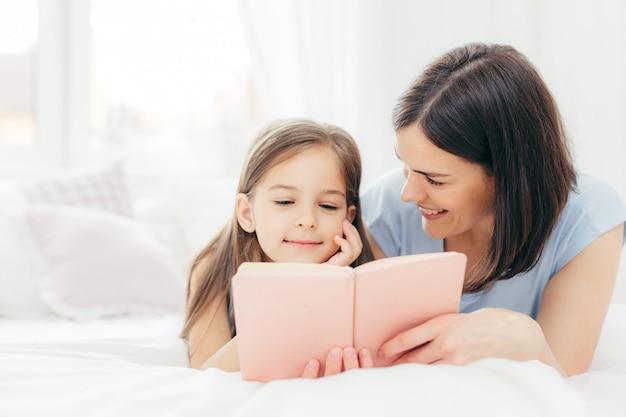 Madre con i capelli scuri, guarda felicemente la sua piccola figlia, legge insieme un libro interessante o una fiaba
