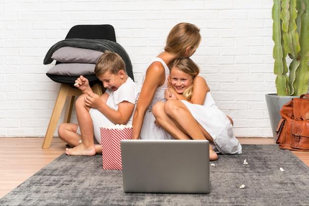 Madre con i suoi due bambini in casa e con i popcorn