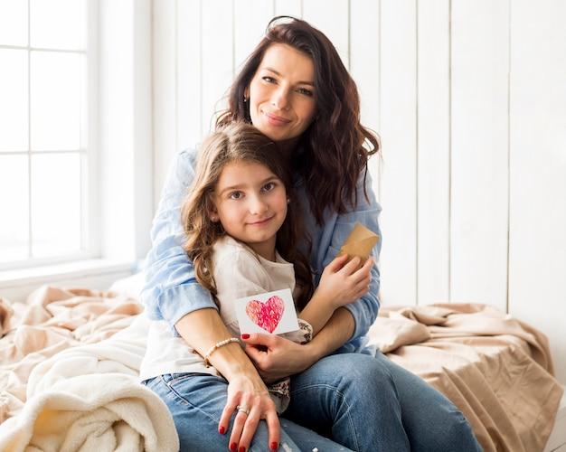 Madre con il disegno del cuore che abbraccia figlia