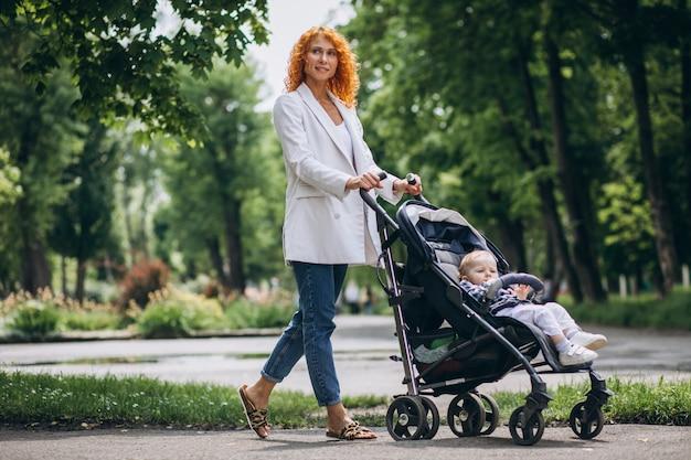 Madre con il figlio piccolo in una carrozzina nel parco