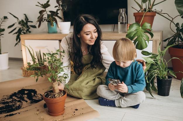 Madre con il piccolo figlio che coltiva le piante a casa