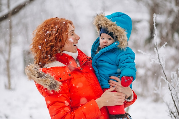 Madre con il suo piccolo figlio insieme in un parco d'inverno