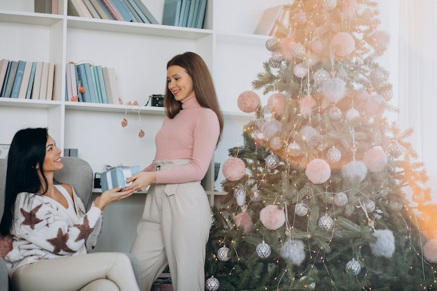 Madre con la figlia adulta con i regali di natale dall'albero di natale