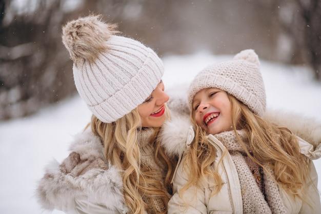 Madre con la figlia che cammina insieme in un parco di inverno