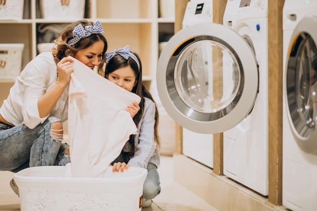 Madre con la figlia che fa lavanderia alla lavanderia automatica del self service