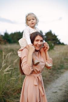 Madre con la figlia che gioca in un campo di autunno