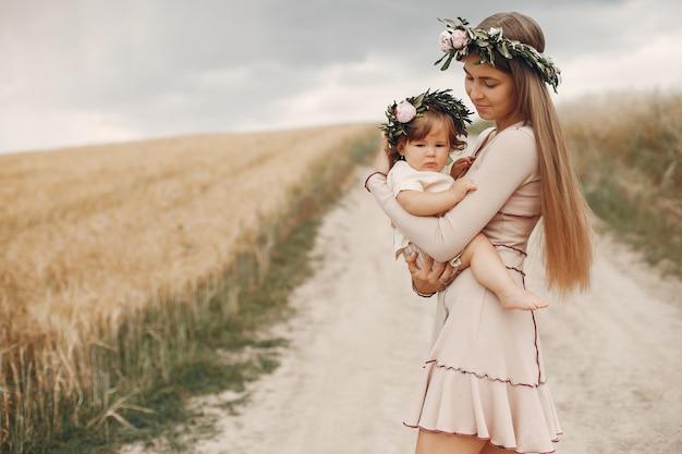 Madre con la figlia che gioca in un campo estivo