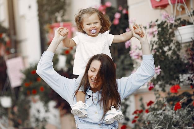 Madre con la figlia che gioca in una città di estate