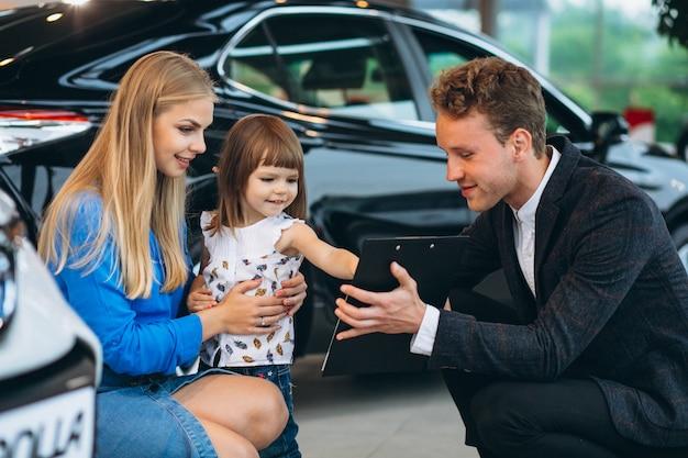 Madre con la figlia che parla con addetto alle vendite in una sala d'esposizione dell'automobile