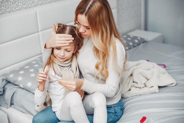 Madre con la figlia di illnes in una camera da letto
