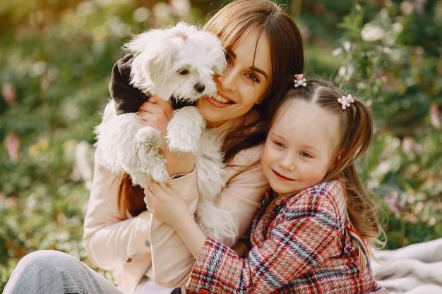 Madre con la figlia in una foresta di primavera con il cane