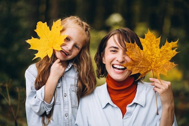 Madre con la figlia piccola nella foresta piena di foglie d'oro