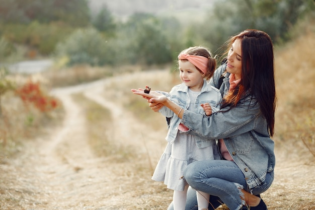 Madre con la piccola figlia che gioca in un campo con una farfalla