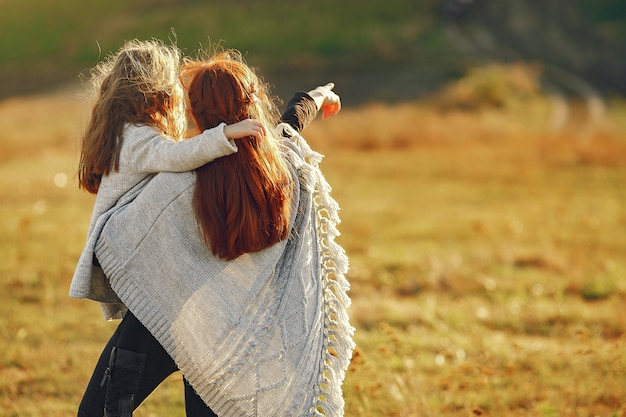Madre con la piccola figlia che gioca in un campo di autunno