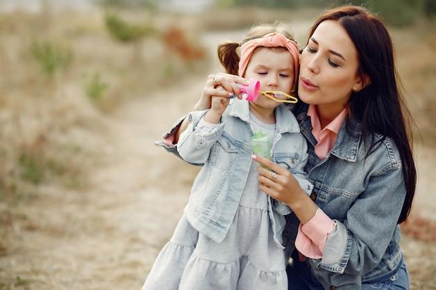 Madre con la piccola figlia che gioca in un campo