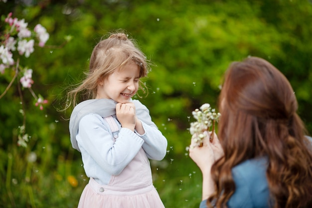 Madre con la piccola figlia che soffia al dente di leone - scena di stile di vita all'aperto nel parco. concetto di famiglia felice