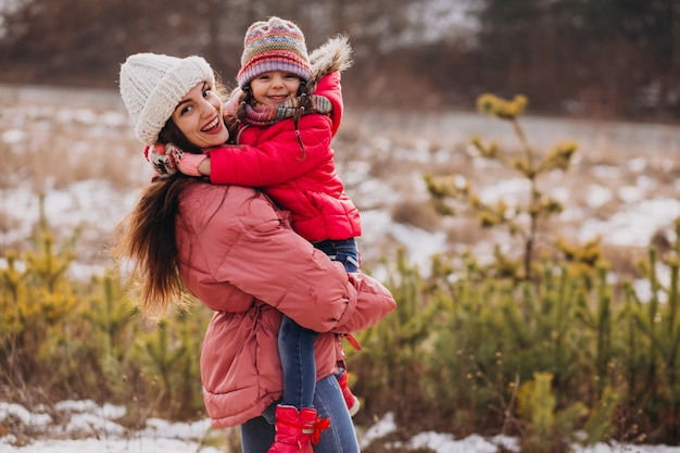 Madre con la piccola figlia in una foresta di inverno