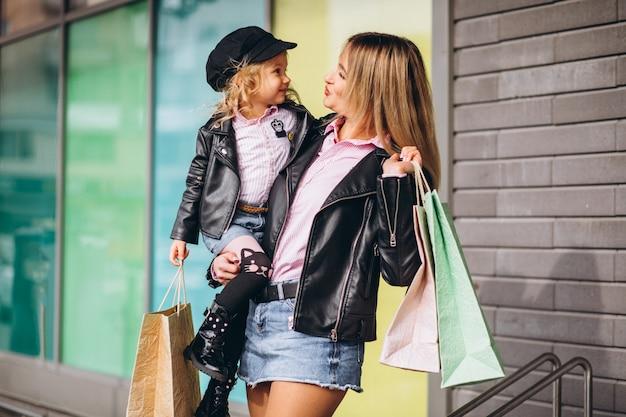 Madre con la sua piccola figlia carina con borse della spesa