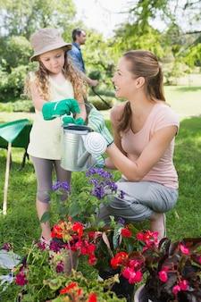 Madre con le piante di innaffiatura della figlia