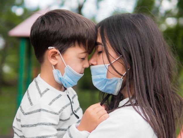 Madre con occhiali da lettura e bambino che indossa maschere mediche