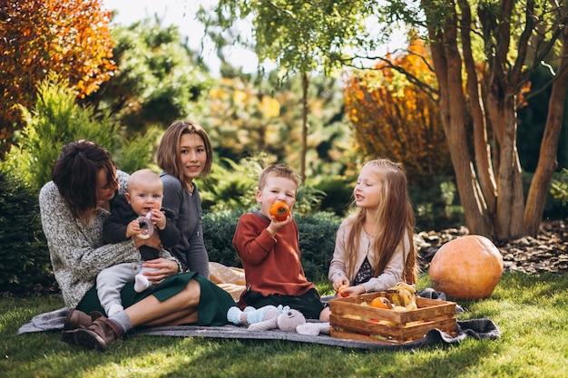 Madre con quattro bambini che hanno picnic sul cortile