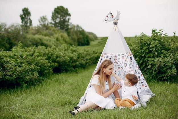 Madre con sonplaying in un campo estivo