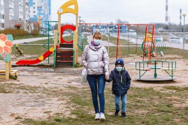 Madre con un bambino nel parco giochi, in maschere mediche