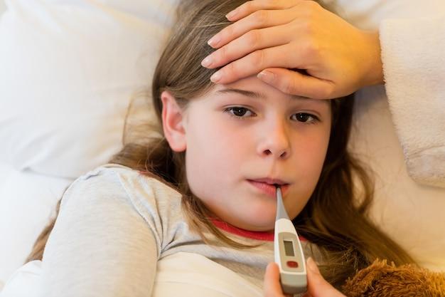 Madre controllando la febbre della figlia in camera da letto