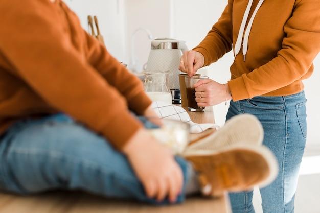 Madre del primo piano che prepara caffè nella cucina