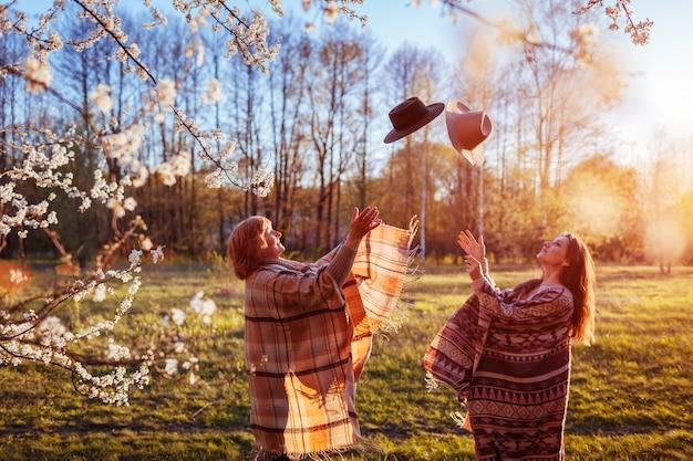 Madre di mezza età e sua figlia adulta gettando cappelli in giardino fiorito. le donne si divertono