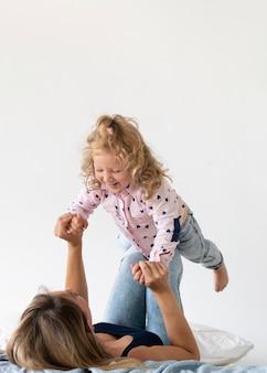 Madre di vista laterale che gioca con la figlia felice
