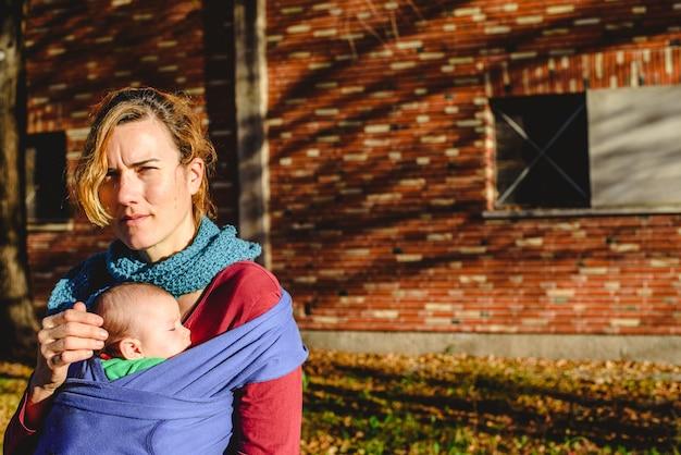 Madre donna che trasportano tranquillamente il suo bambino appena nato in una sciarpa durante una passeggiata al sole.
