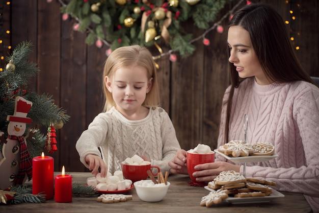 Madre e bambina con i biscotti di natale a casa