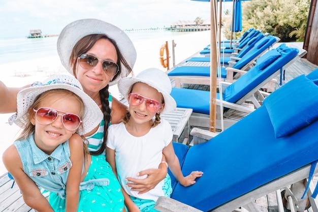 Madre e bambine che prendono selfie alla spiaggia tropicale