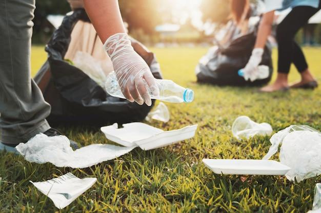 Madre e bambini che tengono la bottiglia di plastica dell'immondizia nella borsa nera al parco alla luce di mattina