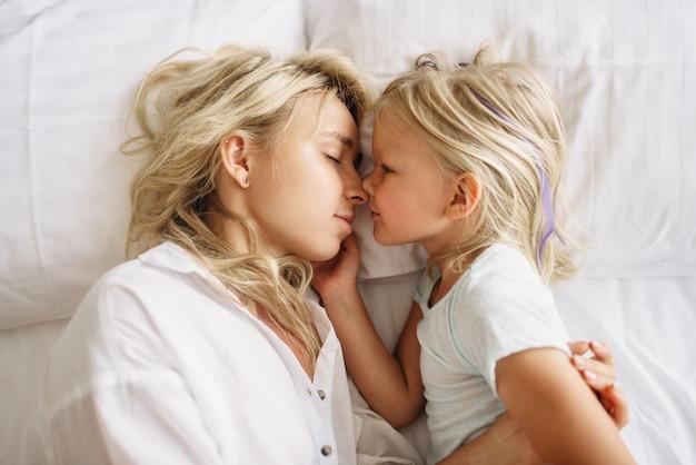 Madre e bambino dorme sul letto a casa, vista dall'alto. sentimento dei genitori, solidarietà, momenti felici