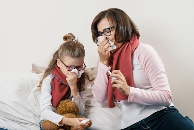 Madre e bambino malati che starnutiscono in fazzoletto