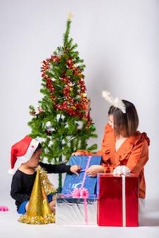 Madre e bambino molto soddisfatti del regalo al giorno natale e felice anno nuovo su sfondo in studio