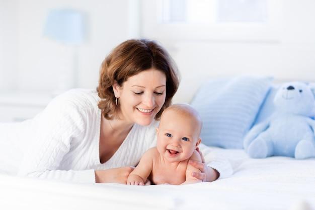 Madre e bambino su un letto bianco