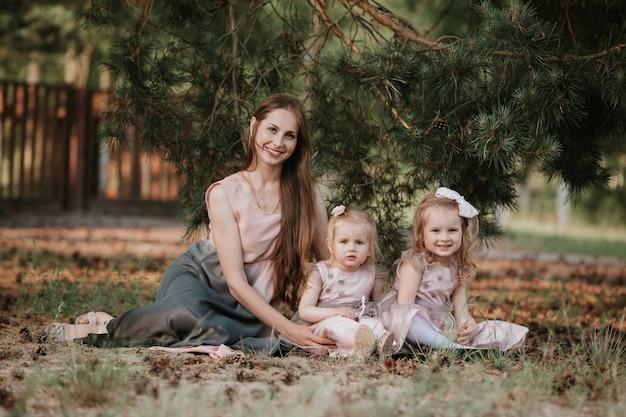 Madre e due figlie vorticose. la madre tiene le figlie sulle mani. tempo di famiglia insieme. un meraviglioso ritratto di mamma con due figlie nel parco