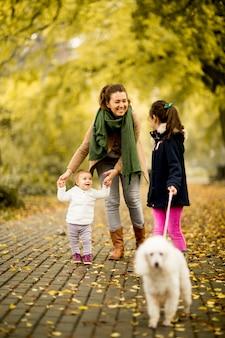 Madre e due ragazze che camminano con un cane nel parco d'autunno
